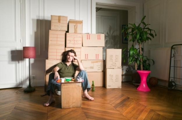 Señor descansando de preparar sus cajas de mudanza por tener el trabajo más cerca de su nuevo domicilio
